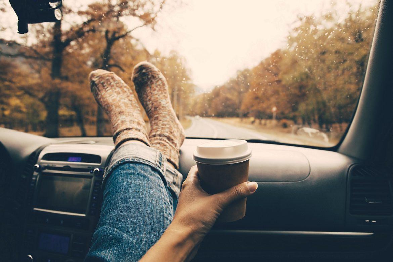 kvinde med benene oppe i bil med en takeaway-kaffe