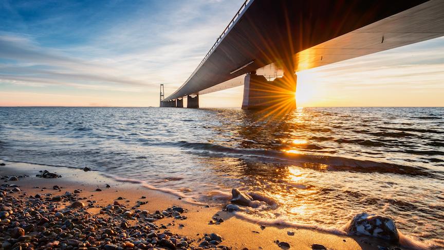 udsigt over storebæltsbroen fra strandkanten i solnedgangens skær